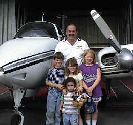 photo of volunteer pilot and plane with children he transported